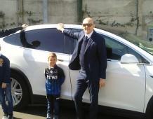 I fratelli Mauro e Gianluigi Piccinini in posa davanti a un modello di auto Tesla, durante l'inaugurazione